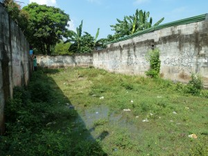 Jezreel School's previous location between two buildings. You can see that the rain has caused flooding.